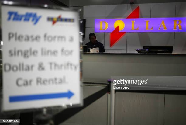 An employee stands behind a Dollar Thrifty Automotive Group Inc rental counter inside Indianapolis International Airport in Indianapolis Indiana US...