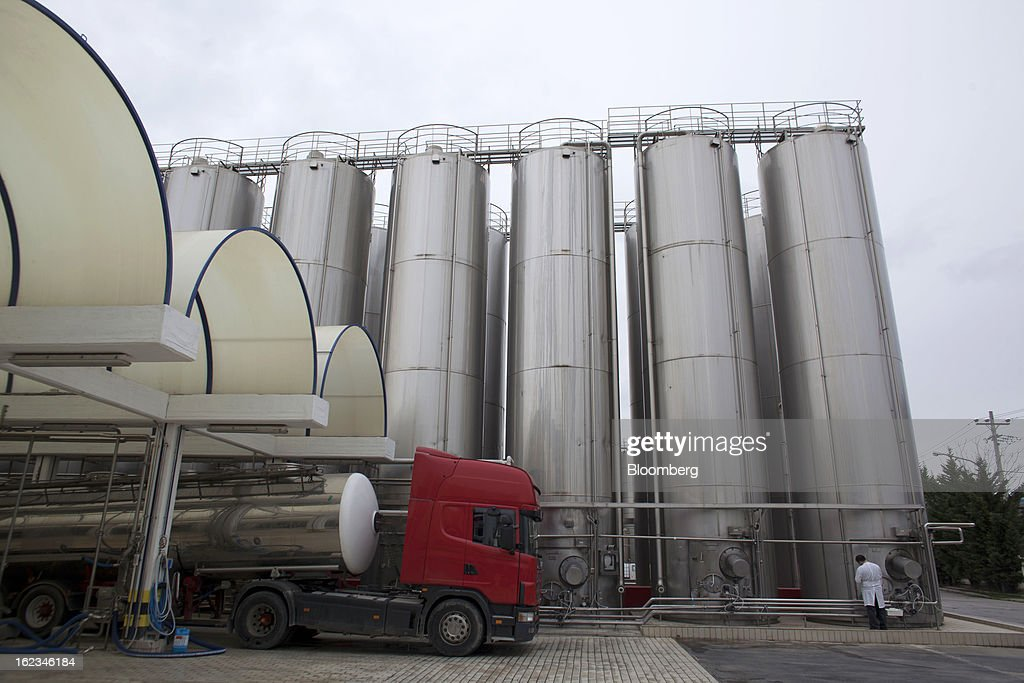 An employee stands beneath storage tanks beside the truck depot at the Fage Dairy Industry SA plant in Athens, Greece, on Thursday, Feb. 21, 2013. An October restructuring that placed Fage International SA's Greek units in a subsidiary called Fage Dairy Industry SA coincided with Coca-Cola Hellenic Bottling SA's plan to flee the epicenter of Europe's debt crisis by moving its main stock listing to London from Athens. Photographer: Kostas Tsironis/Bloomberg via Getty Images