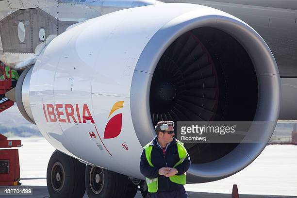 An employee stands by the engine of an Airbus A330300 jet operated by Iberia airlines a unit of International Consolidated Airlines Group SA as it...