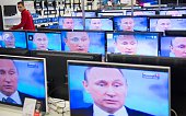 An employee stands by TV sets in a shop in Moscow on April 16 2015 during the broadcast of Russian President Vladimir Putin's annual televised...