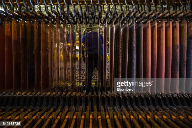 An employee stands in front of a machine moving copper anodes and cathodes during the electrolytic refining process at the Southern Copper Corp...