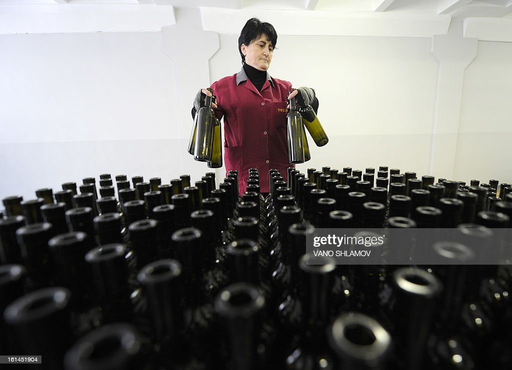 An employee stands in front of bottles at a winery in Tbilisi, on February 11, 2013. Georgian officials held recently talks in Moscow to agree a mechanism on lifting the Russian trade embargo on Georgian wine and mineral water.