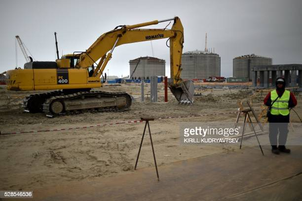 An employee stands in front of natural gas reservoirs under construction at the port of Sabetta in the Kara Sea shore line on the Yamal Peninsula in...