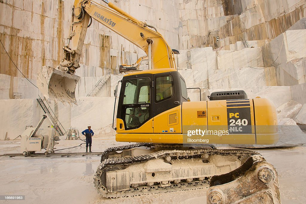 An employee stands near a bulldozer operating on the extraction floor of a marble quarry pit operated by Bloco B in Pardais, Vila Vicosa, Portugal, on Wednesday, April 17, 2013. Portugal is posting its first trade surplus in at least six decades, which may help vindicate a strategy of front-loading austerity to deliver economic reform. Photographer: Mario Proenca/Bloomberg via Getty Images
