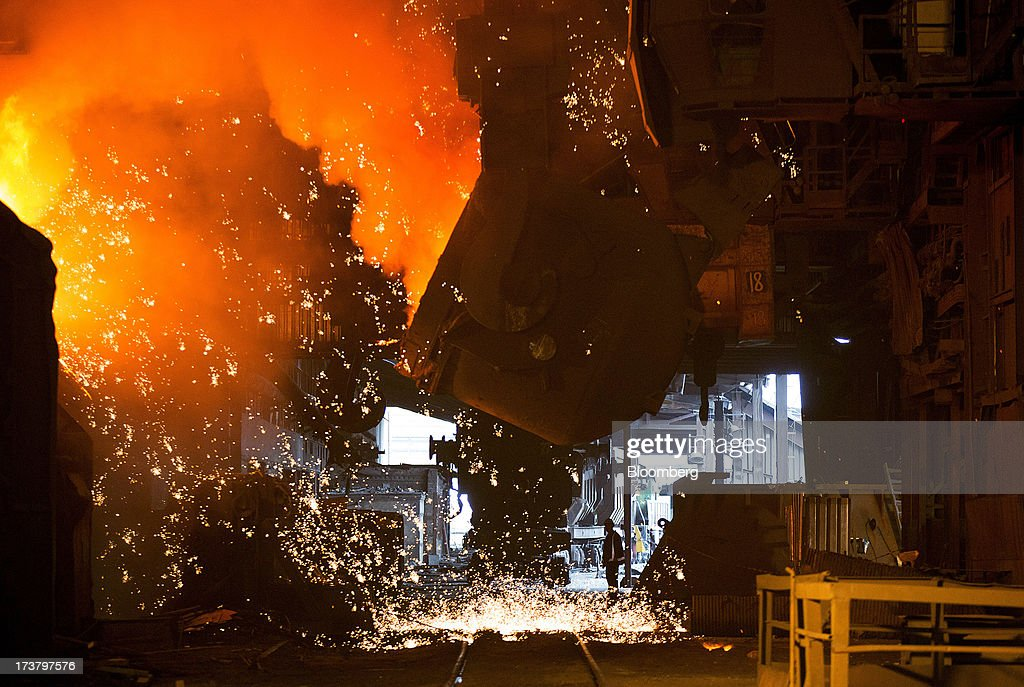 An employee stands near a cauldron of molten metal in the converter shop at OAO Mechel's metallurgical plant in Chelyabinsk, Russia, on Wednesday, July 17, 2013. Mechel, the country's largest producer of coking coal for steelmakers has begun operating its $700m rail production line which can produce 100 meter rails. Photographer: Andrey Rudakov/Bloomberg via Getty Images