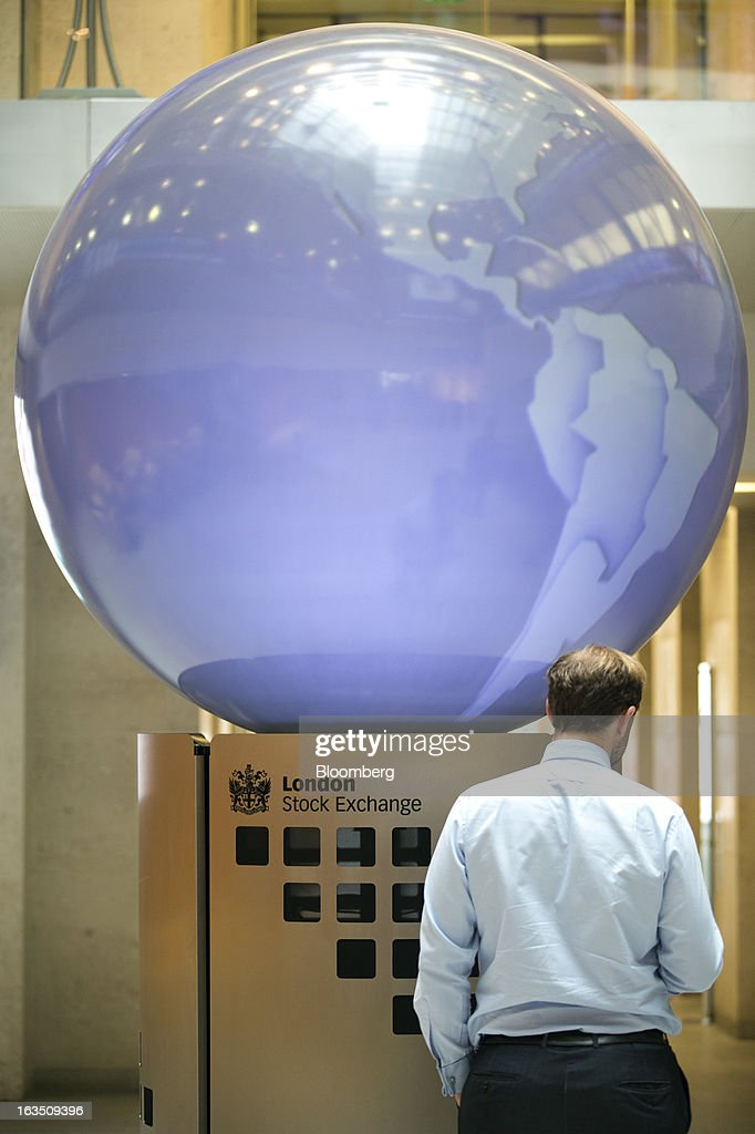 An employee stands near an interactive sculpture inside the London Stock Exchange Group Plc's (LSE) headquarters in London, U.K., on Monday, March 11, 2013. European stocks fell from a 4 1/2-year high as Fitch Ratings downgraded Italy and China's retail sales and industrial output missed forecasts. Photographer: Jason Alden/Bloomberg via Getty Images