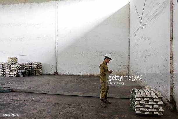 An employee stands near bars of tin in the warehouse of a tin smelter owned by Johan Murod a private tin refiner in Pangkal Pinang Bangka Island...