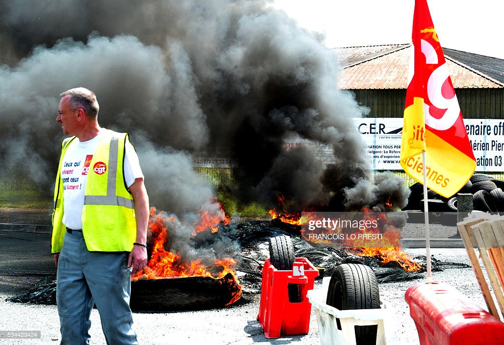 An employee stands next to a fire and French CGT union's flag as employees block the access of the PSA plant on May 26, 2016 in Valenciennes, northern France during a protest against the government's labour market reforms. The French government's labour market proposals, which are designed to make it easier for companies to hire and fire, have sparked a series of nationwide protests and strikes over the past three months. / AFP / FRANCOIS