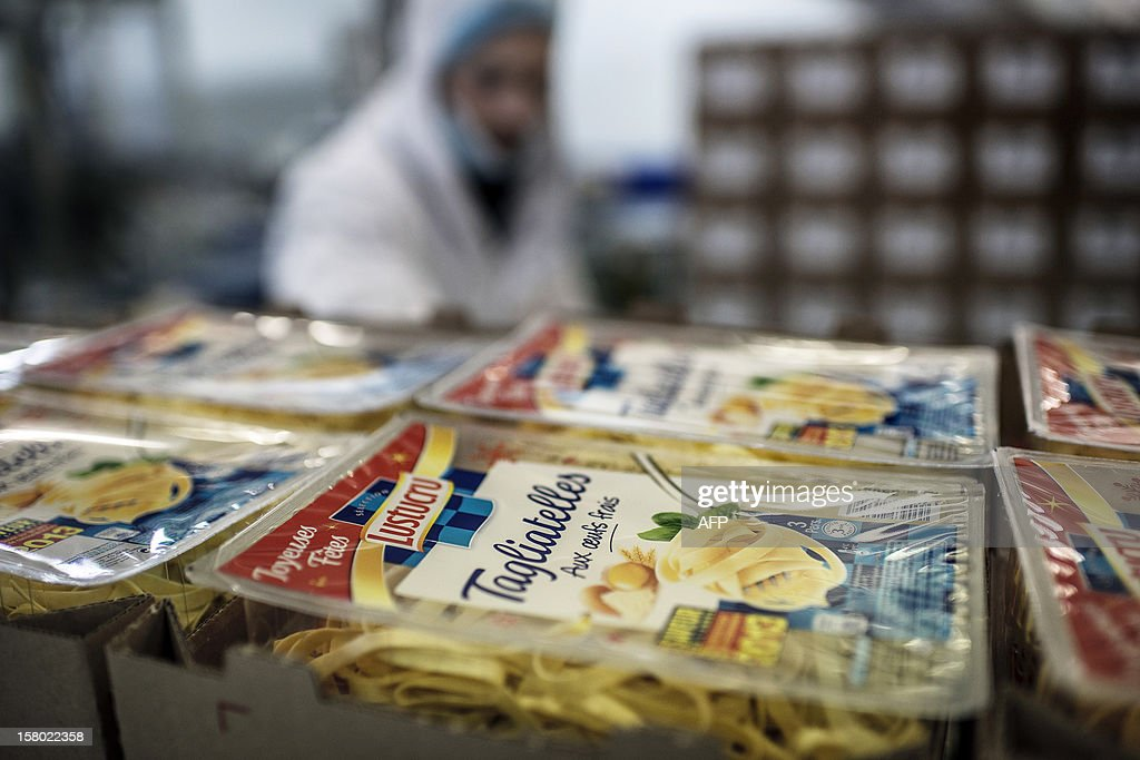 An employee stands next to boxes of raviolis to be stored, on November 21, 2012 on the production line of French pasta manufacturer Lustucru at the Saint-Genis Laval plant. AFP PHOTO / JEFF PACHOUD