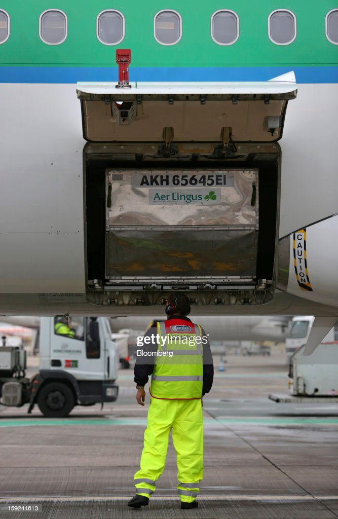 An employee stands next to the open cargo door of an Airbus A320 aircraft, operated by Aer Lingus Group Plc, at Gatwick airport in Crawley, U.K., on Thursday, Jan. 10, 2013. Gatwick, acquired by Global Infrastructure Partners Ltd. in 2009 after regulators sought a breakup of BAA Ltd., owner of the larger Heathrow hub, is 30 miles (48 kilometers) south of London and serves about 200 destinations, more than any other U.K. airport, according to flight schedule data provider OAG. Photographer: Chris Ratcliffe/Bloomberg via Getty Images