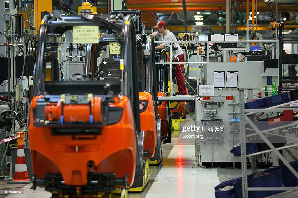An employee stands on a platform to work on a Linde H35 forklift truck as its sits on the production line at the Linde Material Handling GmbH factory, a unit of Kion Group AG, in Aschaffenburg, Germany, on Tuesday, Nov. 12, 2013. Kion Group AG, the German forklift-maker which listed shares in June, is looking to expand its global sales network via acquisitions to catch up with main competitor Toyota Industries Corp. Photographer: Krisztian Bocsi/Bloomberg via Getty Images