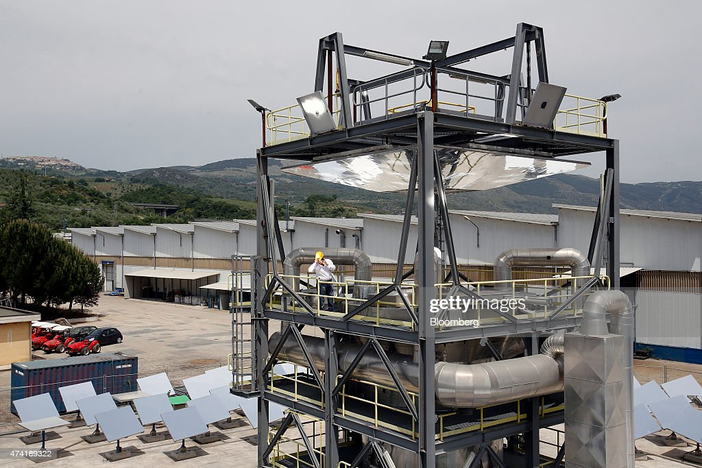 An employee stands on a raised platform of a solar generation unit as heliostat panels reflect sunlight below at a Solar Thermoelectric Magaldi (STEM) pilot plant, operated by Magaldi Group, in Buccino, Italy, on Monday, May 18, 2015. The project captures the energy of the sun which is transferred via the generation unit to heat retaining silica sand, producing steam that powers a turbine and is suitable for use in systems operating over a large temperature range. Photographer: Alessia Pierdomenico/Bloomberg via Getty Images