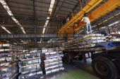 An employee stands on a truck loaded with steel sheets in the tube mill at the manufacturing facility of Uttam Galva Steels Ltd the Indian unit of...