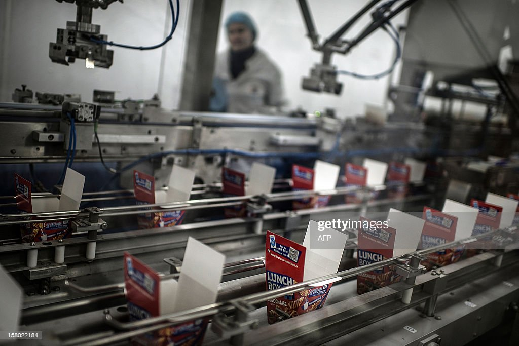 An employee stands, on November 21, 2012, past a production line of French pasta manufacturer Lustucru at the Saint-Genis Laval plant.