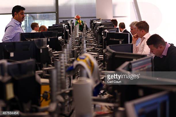 An employee stands up to talk to a colleague at the offices of Panmure Gordon and Co on October 20 2014 in London England Markets stabilised over the...