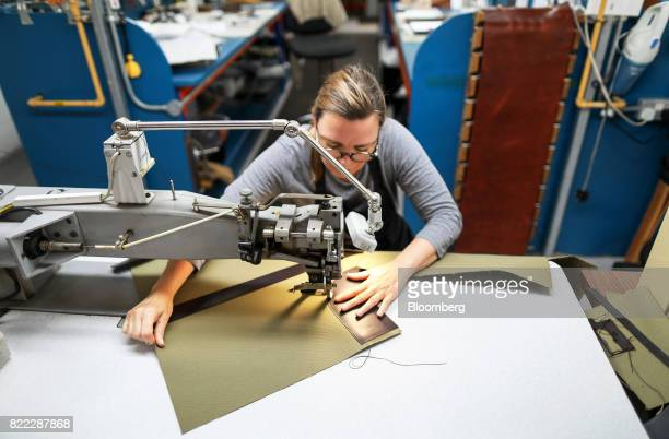 An employee stitches leather sections to a Kempton canvas tote bag at the Alfred Dunhill Ltd London Leather Workshop in London UK on Tuesday July 25...