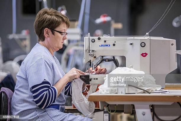 An employee stitches women's underwear garments with a sewing machine on the production line of fine lingeriemaker Allande in Le Dorat France on...