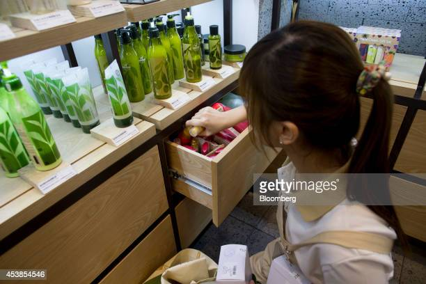 An employee stocks a shelf at Amorepacific Corp's Innisfree store in the Causeway Bay district of Hong Kong China on Wednesday Aug 20 2014 Sales in...