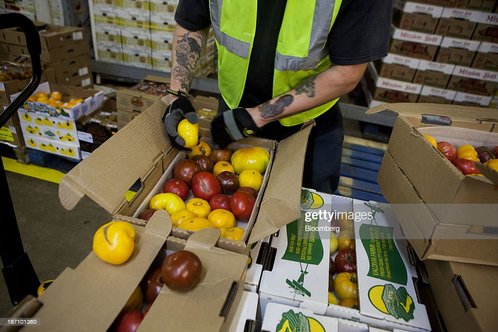 An employee stocks heirloom tomatoes at the Specialty Produce warehouse in San Diego, California, U.S., on Friday, Nov. 1, 2013. The U.S. Bureau of Economic Analysis is scheduled to release gross domestic product (GDP) figures on Nov. 7. Photographer: Sam Hodgson/Bloomberg via Getty Images