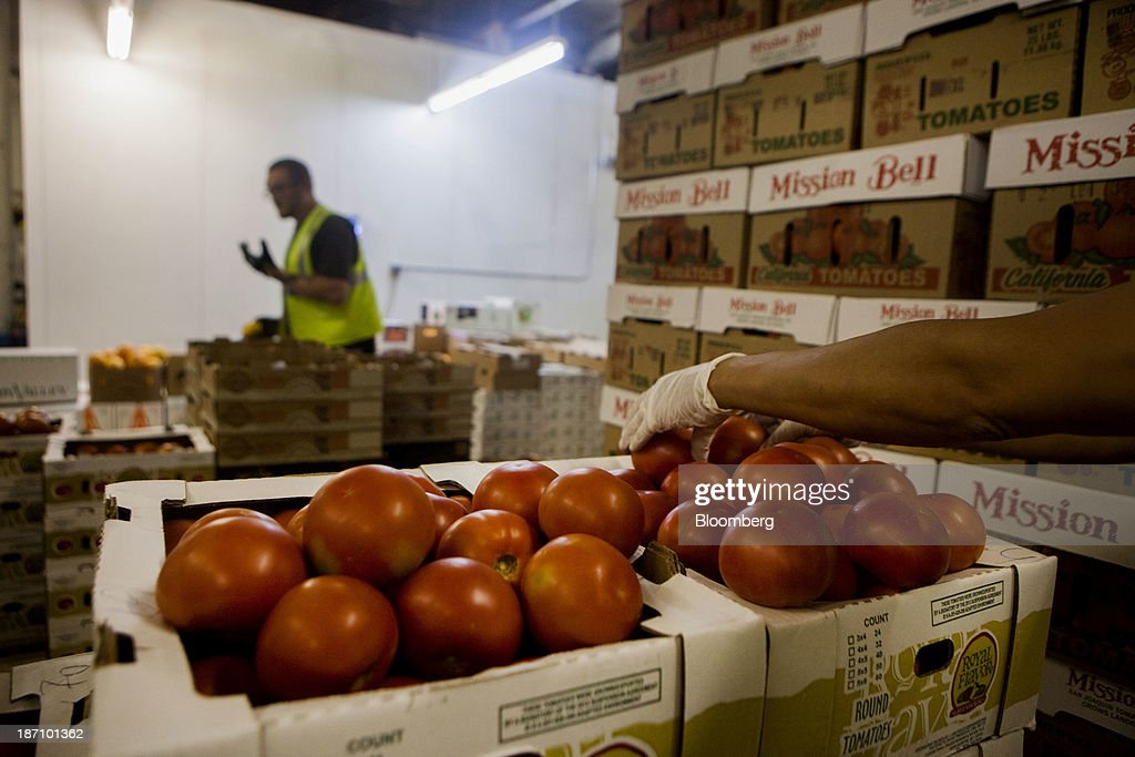 An employee stocks tomatoes at the Specialty Produce warehouse in San Diego, California, U.S., on Friday, Nov. 1, 2013. The U.S. Bureau of Economic Analysis is scheduled to release gross domestic product (GDP) figures on Nov. 7. Photographer: Sam Hodgson/Bloomberg via Getty Images