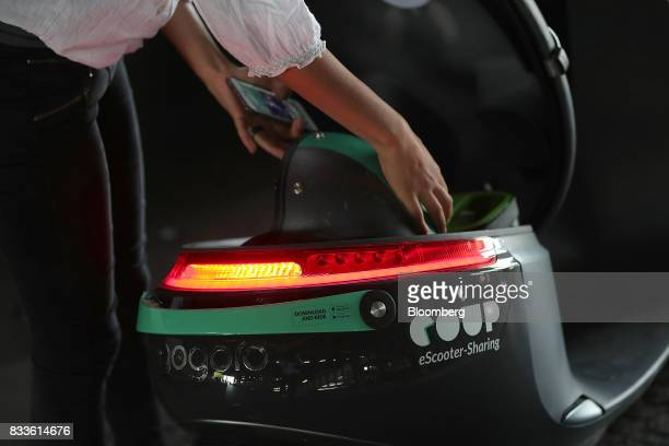 An employee stows a crash helmet in the underseat storage compartment of a Coup eScooter electric hire vehicle operated by Robert Bosch GmbH in...