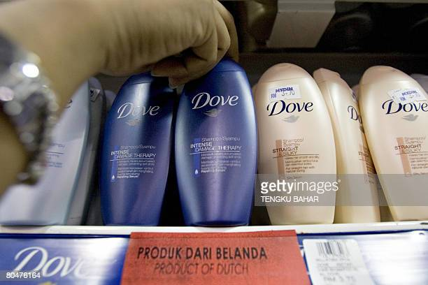 An employee straightens a row of Dove shampoo bottles a product of AngloDutch company Unilever above a red tag identifying them as a Dutch product at...
