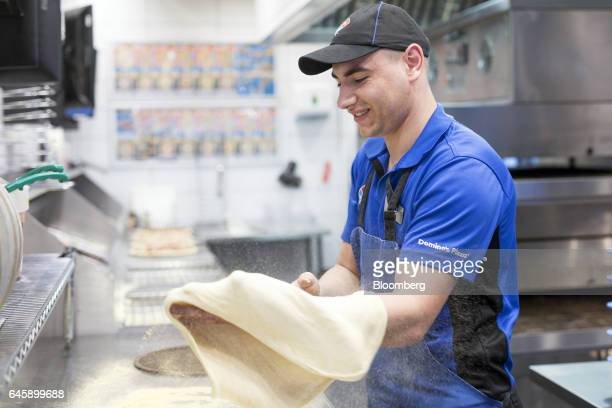 An employee stretches dough by hand for a pizza base inside a Domino's Pizza Group Plc store in Hanwell London UK on Monday Feb 27 2017 Domino's...