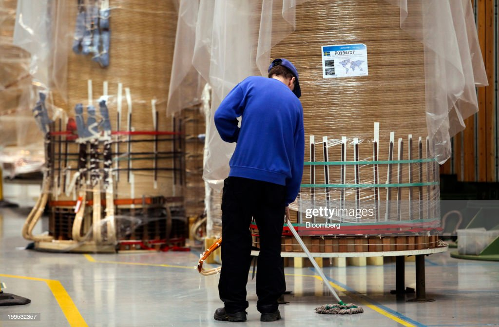An employee sweeps the floor near electrical coils manufactured for use in industrial power transformers at Alstom SA's factory in Stafford, U.K., on Tuesday, Jan. 15, 2013. Alstom surged 29 percent in Paris trading in 2012, beating the 15 percent gain of the the French benchmark CAC 40 Index. Photographer: Chris Ratcliffe/Bloomberg via Getty Images