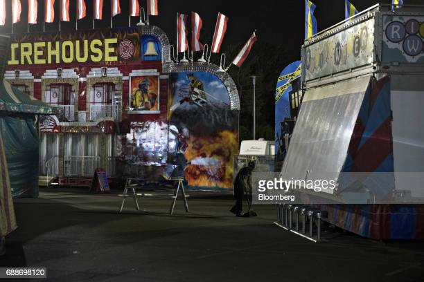 An employee sweeps the ground after closing during the Dreamland Amusements carnival in the parking lot of the Neshaminy Mall in Bensalem...