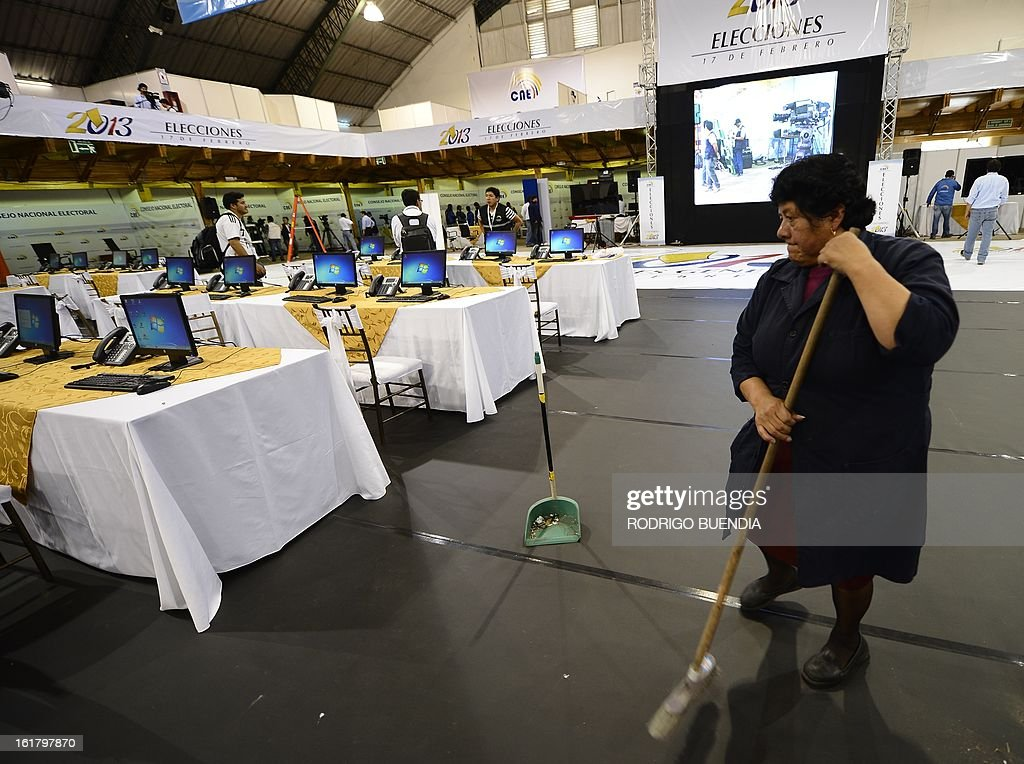 An employee sweeps the place as members of the National Election Council (CNE) check final details on the eve of general elections in Quito on February 16, 2013. Almost 12 million people are eligible to vote in Ecuador's presidential election, with President Rafael Correa tipped to win re-election by a landslide. AFP PHOTO / RODRIGO BUENDIA