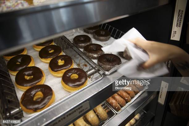 An employee takes a chocolate donut off a display tray for a customer at a Dunkin' Donuts Inc location in Los Angeles California US on Wednesday Sept...
