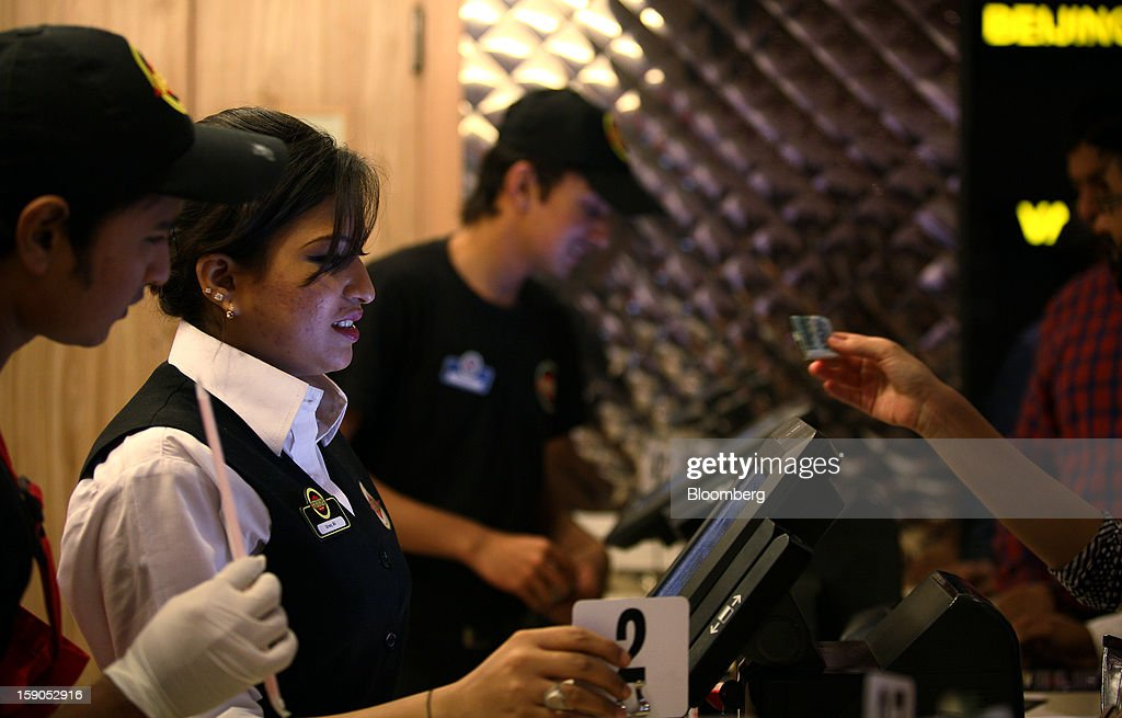 An employee takes a customer's order at a Fatburger outlet in Karachi, Pakistan, on Saturday, Jan. 5, 2013. Fatburger opened its first outlet in Pakistan to the public on Jan. 5. Photographer: Asim Hafeez/Bloomberg via Getty Images