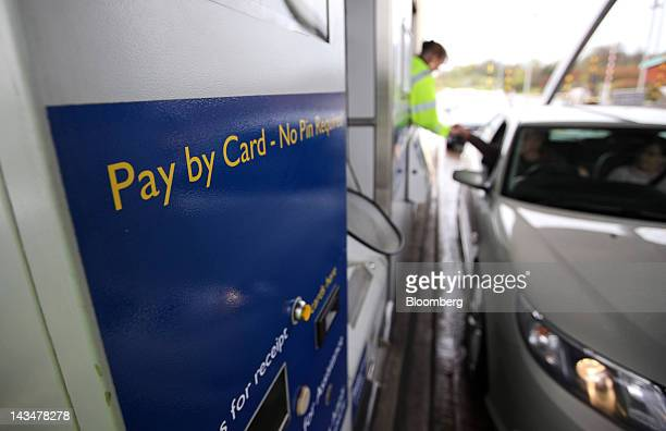 An employee takes a payment from a driver at the Great Wyrley payment booths part of the M6 motorway toll road operated by Midland Expressway Ltd...