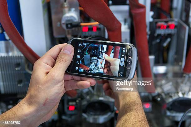 An employee takes a photograph with a Samsung Electronics Co smartphone which will be sent onto a service operator for diagnostic problem solving...