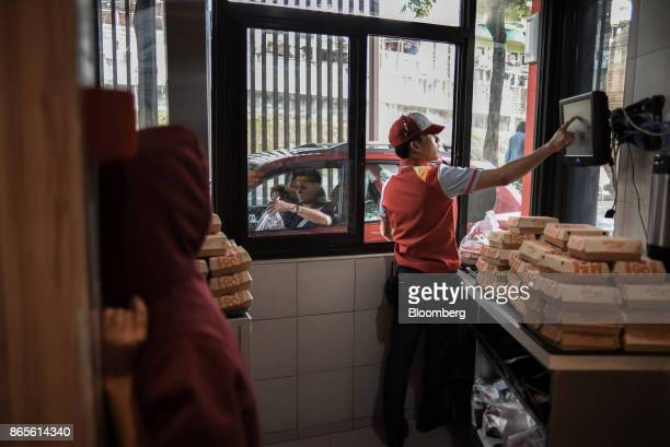 An employee takes an order from a drivethrough customer at a Jollibee Foods Corp restaurant in the Bonifacio Global City triangle area of Manila the...