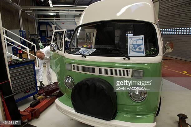 An employee takes apart the inside of a Volkswagen T2 aka kombi or bulli camping van aka kombi or bulli preparing it for renovation at a Volkswagen...