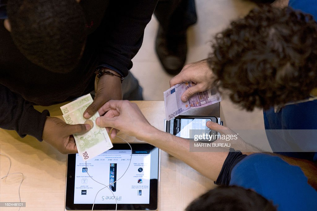 An employee takes euro banknotes from customers purchasing an Apple's new iPhone 5 smartphone at a cash register in an Apple store, on September 21, 2012 in Paris. The iPhone 5 goes on sale on September 21, 2012 in the United States, Canada, Britain, France, Germany, Australia, Hong Kong, Japan and Singapore.