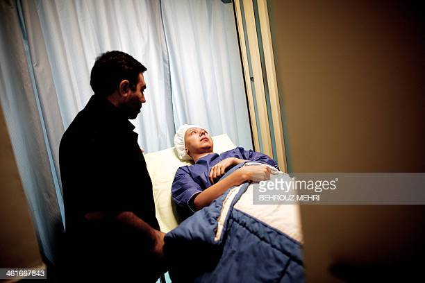 An employee takes Iranian breast cancer patient Farvah to the operation room in an elevator for a mastectomy operation which was turned to a...