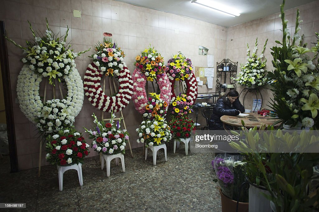 An employee takes orders for wreaths in a funeral flower store in Madrid, Spain, on Monday, Dec. 17, 2012. Spain, responding to street protests and reports of suicides linked to foreclosures, introduced rules to help protect families from eviction, increasing the risk of creditor losses and weakening an already fragile banking system. Photographer: Angel Navarrete/Bloomberg via Getty Images