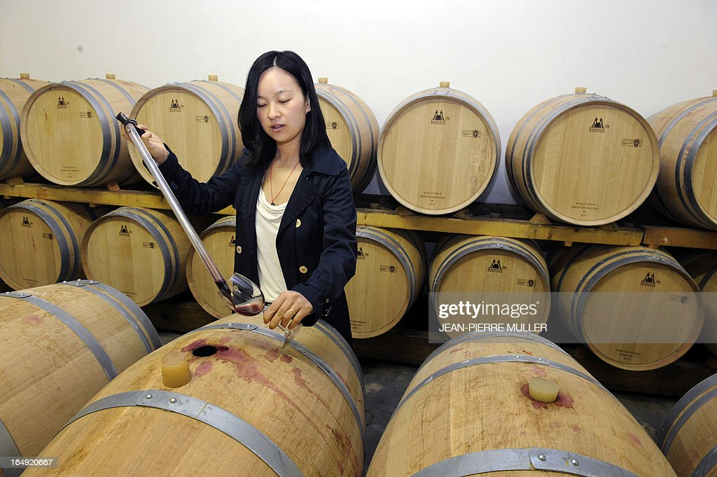 An employee takes some wine out of a barrel in the warehouse of the Chateau Laulan-Ducos, a cru bourgeois wine of Bordeaux's Medoc region, owned by Chinese jewelry chain TESiRO's head Richard Shen (Shen Dongjun), on March 29, 2013 in Jau-Dignac-et-Loirac.