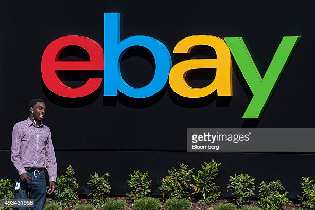 An employee talks on a mobile phone in front of eBay Inc signage displayed at the company's headquarters in San Jose California US on Friday Oct 16...