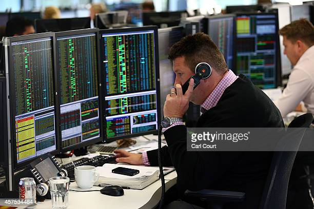 An employee talks on the phone as he views trading screens at the offices of Panmure Gordon and Co on October 20 2014 in London England Markets...