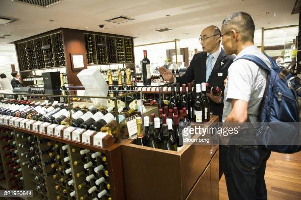 An employee talks to a customer about French wine at the Isetan Shinjuku department store operated by Isetan Mitsukoshi Holdings Ltd left in Tokyo...