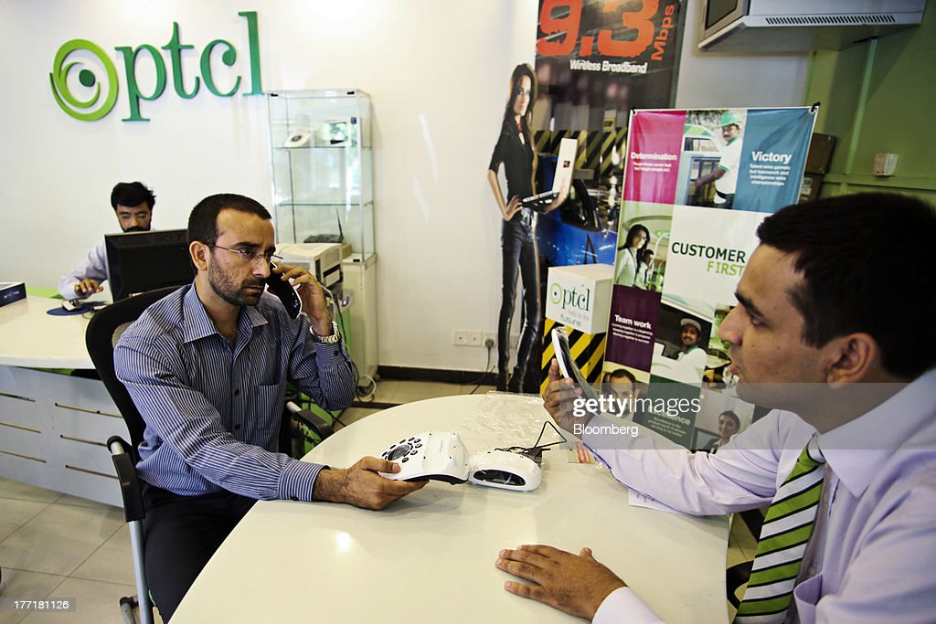 An employee talks to a customer about the features of a telephone on sale at the Pakistan Telecommunications Co. (PTCL) sales and customer care center in Islamabad, Pakistan, on Wednesday, Aug. 21, 2013. Pakistan Telecommunication, the countrys biggest fixed-line phone-service provider, said second-half sales growth will at least match the pace of the previous six months as broadband demand increases. Photographer: Asad Zaidi/Bloomberg via Getty Images
