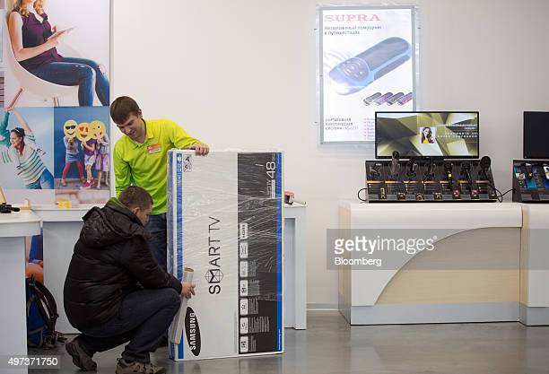 An employee talks to a customer as he wraps a boxed Smart TV television manufactured by Samsung Electronics Co inside an order fulfillment centre...