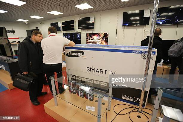 An employee talks to a customer beside a boxed Smart TV television manufactured by Samsung Electronics Co inside an MVideo store in Saint Petersburg...