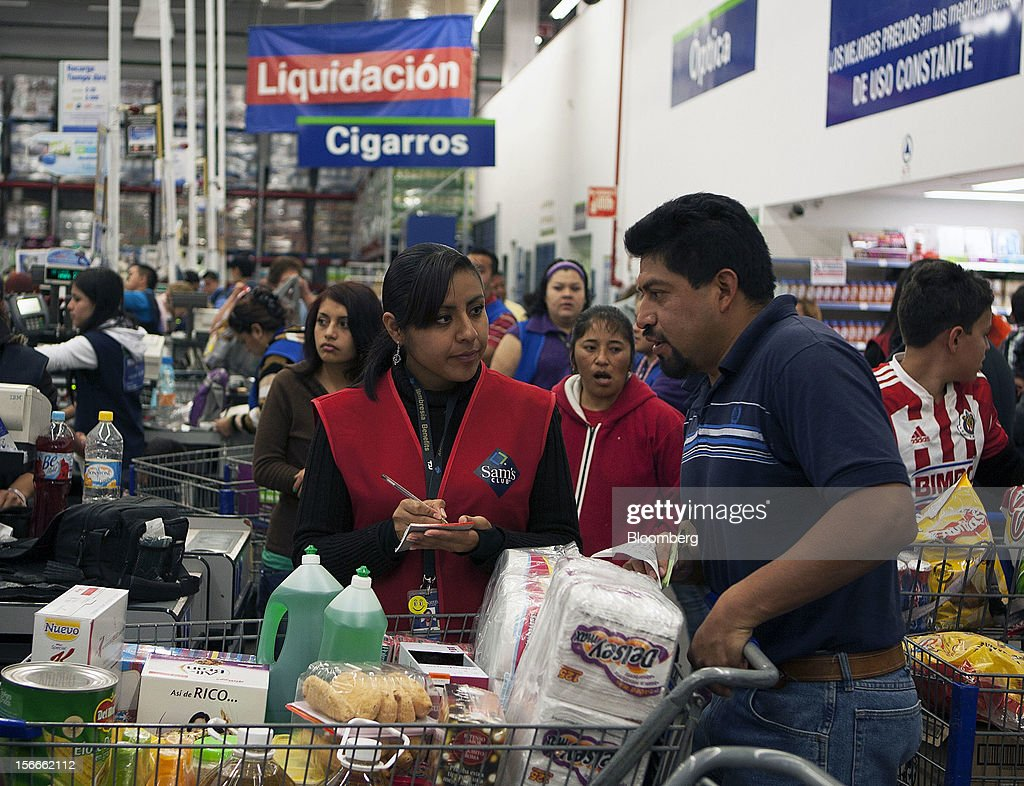 An employee talks to a shopper with a cart filled with merchandise inside a Sam's Club store in Mexico City, Mexico on Saturday, Nov. 17, 2012. El Buen Fin, Mexico's equivalent of Black Friday, when the year's biggest discounts are offered by participating stores, is held on the third weekend of November and will run through Nov. 19. Photographer: Susana Gonzalez/Bloomberg via Getty Images