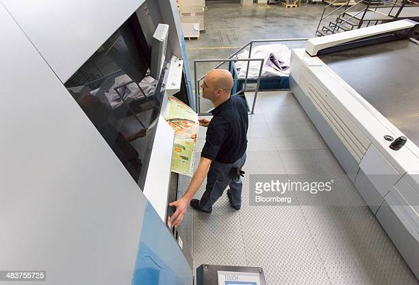An employee tests a Heidelberg Speedmaster industrial printing press at the Heidelberger Druckmaschinen AG manufacturing hall in Wiesloch Germany on...