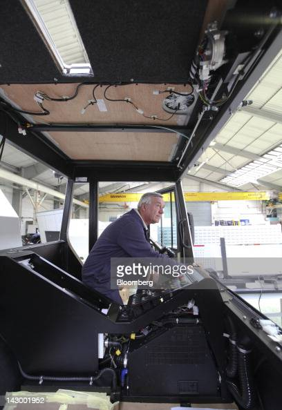 An employee tests electrical components inside the drivers cab section of an aviation towing tractor at the Douglas Equipment plant owned by...