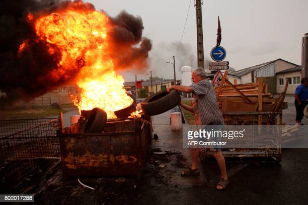 An employee throws a tyre into a fire outside the plant of the GMS company on June 27 2017 in La Souterraine central France Around 280 jobs are on...